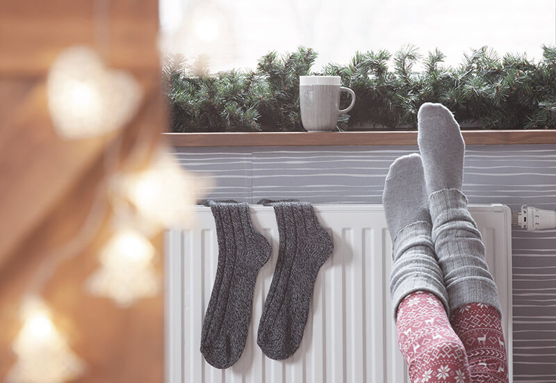 Cozy socks on heater with holiday decor around