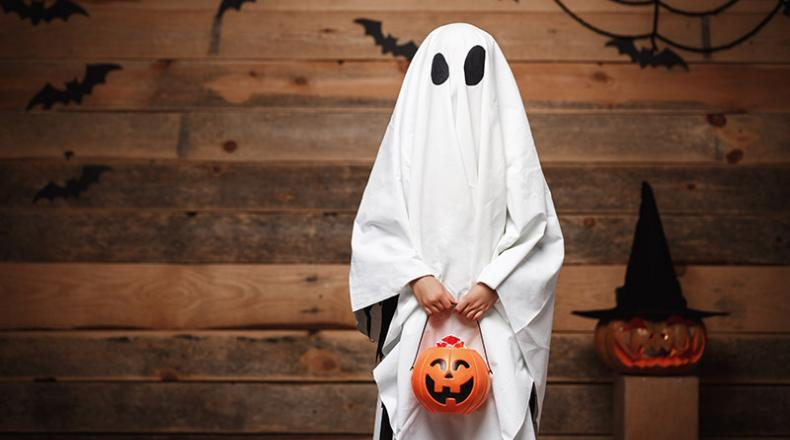 Kid dressed as ghost holding a jack-o-lantern